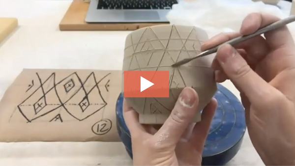 Still from video of Katie Bosley drawing pattern on cup.